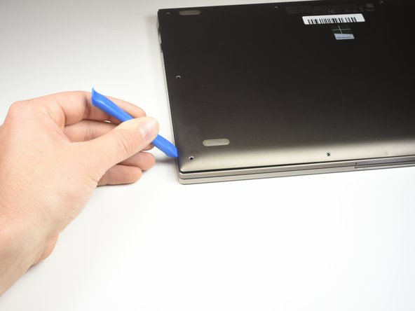開口ツールをバックカバーの下に差し込んでスライドして、カバーを持ち上げます。