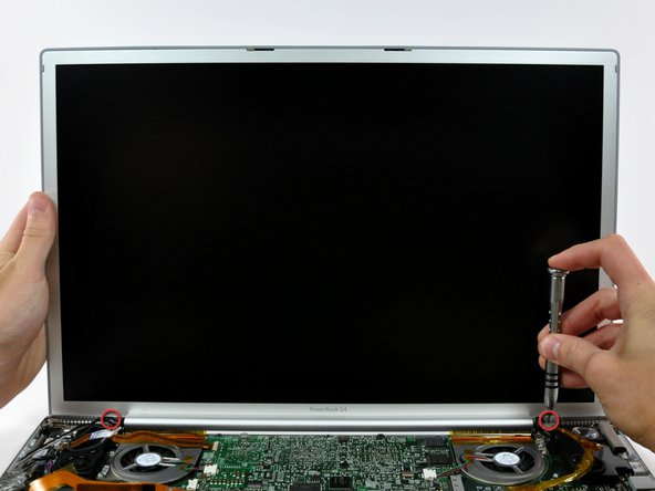 Image 1/1: While supporting the display with one hand, remove the one remaining T6 10 mm Torx screw from each display bracket (two screws total).