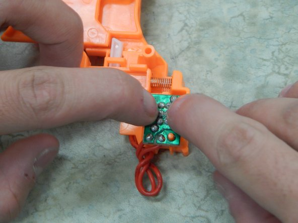 Find the two plastic clasps and position your hands so you can pry them open with your fingers. We recommend that you try and pry them open without removing the piece so you can feel how fragile the plastic is.