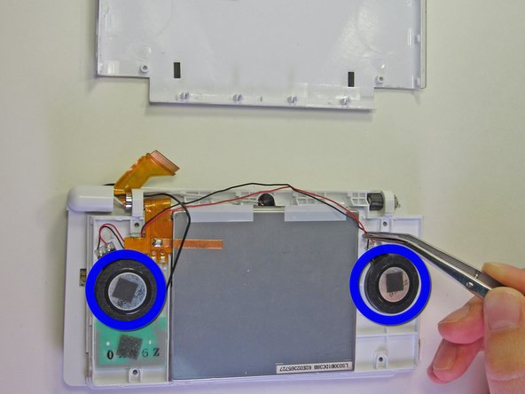 Carefully remove the two speakers and the green wireless card from the top panel.