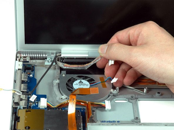 Peel up the iSight and inverter cables which are attached with a mild adhesive above the left fan.