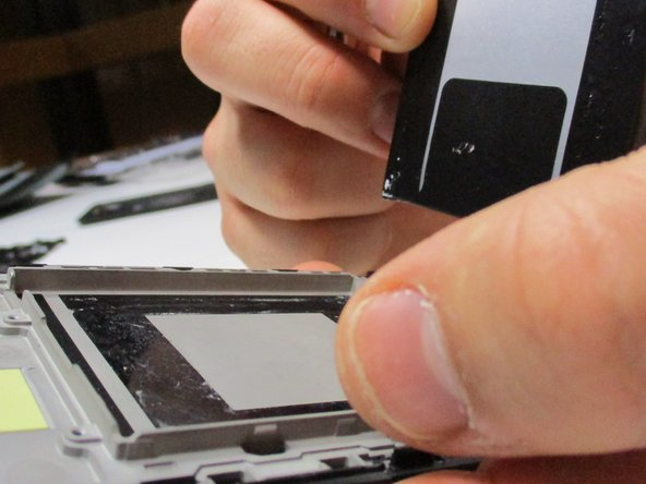 Image 2/3: Apply enough pressure to release the battery from the adhesive holding it to the phone.