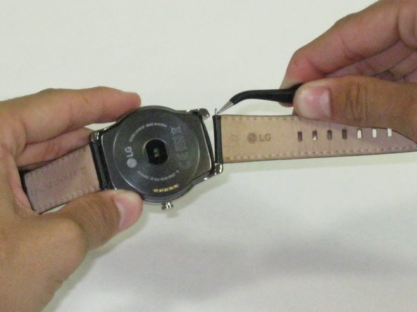 Image 2/2: Using '''tweezers''', remove the pins, one on each side, in order to only leave the face of the watch.