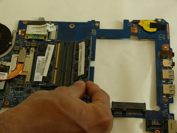 After RAM memory card is released from the motherboard, hold the RAM  card on a 45 degree angle and remove the card.