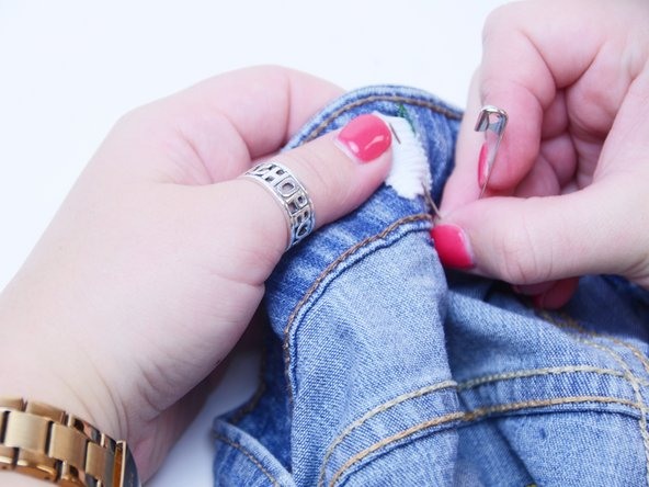 Similar to the process in step 6, attach the elastic strip just outside of the cut using the remaining safety pin.