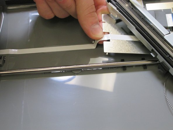 Gently unpeel the ribbon cable from the bottom of the case.