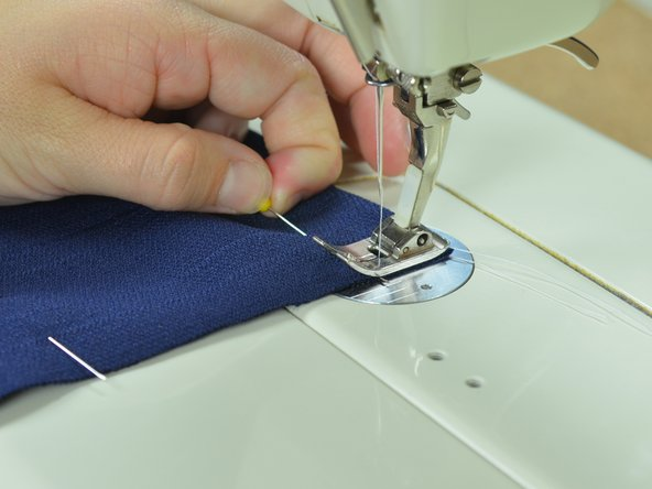 Depress the pedal and sew slowly forward, guiding the fabric with your hands as you go.