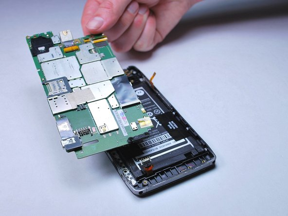Image 3/3: Work your way around the entire edge of the motherboard to release it and remove it from the back of the phone.