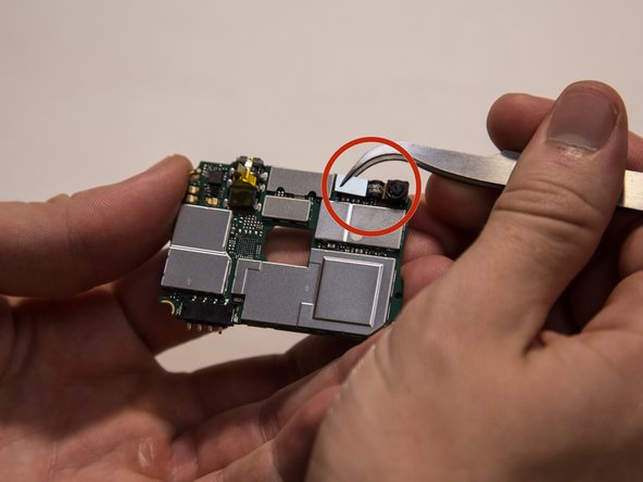 Image 2/2: There is a silver connector and a black flex cable attached to the front camera.