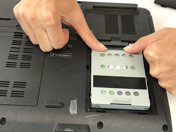 Push the hard drive out of its housing as shown.