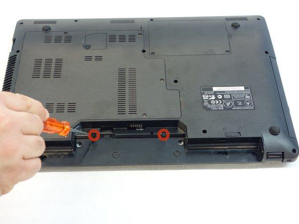 A l'aide du tournevis Phillips #1, dévissez les deux vis qui se trouvent dans le logement de la batterie (accumulateur) de l'ordinateur. Elles fixent par derrière le cache au-dessus du clavier. NB: Elles sont plus courtes que les autres et d'un diamètre inférieur.