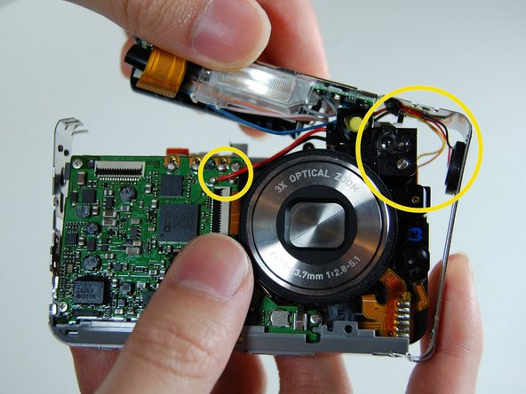 Image 1/3: At the bottom of the camera the L shaped frame is being held in by two plastic bumps and a metal tab.