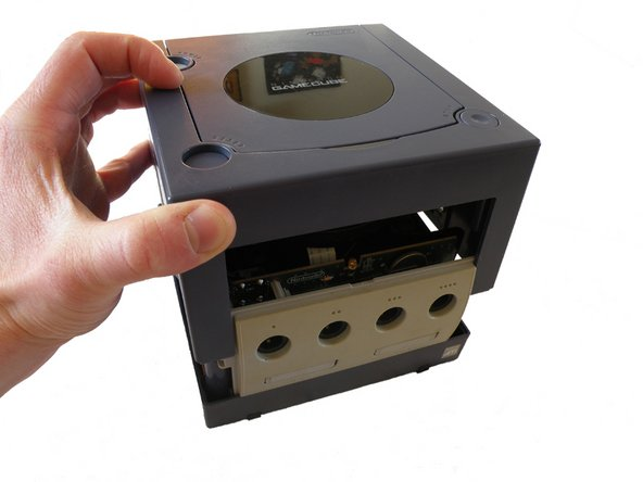 Using both hands, grasp the top of the Gamecube and carefully slide off the top wall exposing the inside of the unit.