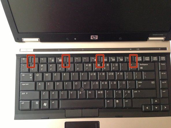 Image 2/3: Slide the retention clips toward the keyboard to release the keyboard