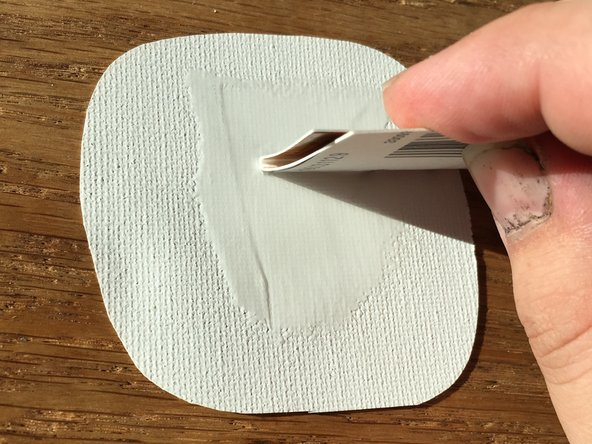 Apply your glue to the white side of the repair piece of canvas and follow up with the cardboard square to spread the glue around on the canvas. An even layer of glue is preferred and should cover the entire piece of canvas.
