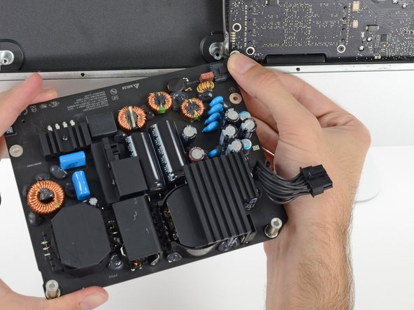 Flip the top of the power supply towards you, like opening a mailbox, to reveal the AC inlet cable connector.