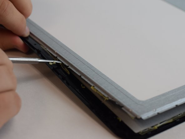 Using the sharp end of the pry tool, separate the plastic from the screen.