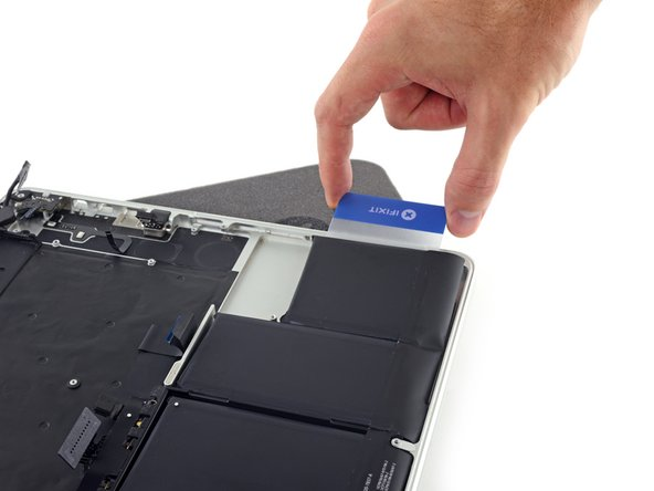 Slide one corner of your plastic card underneath the second battery cell.