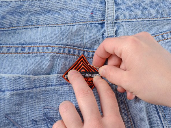Pin the patch to the jeans.