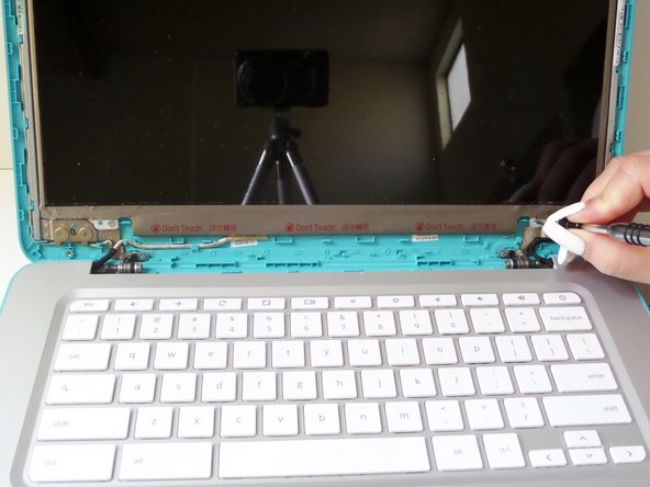Remove the four 4mm screws within the metal tabs on the top and bottom of the screen using a Phillips Head 1 screwdriver.