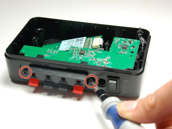 Use a Phillips #1 screwdriver to unscrew the two 10 mm screws located on either side of the speakers.