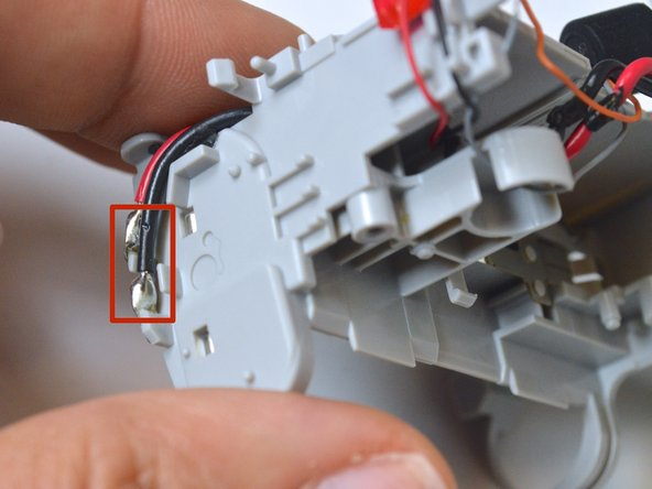 Use the soldering iron to remove the red and black wires from the battery contacts.