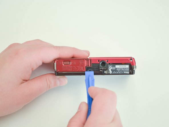 Use a plastic opening tool to carefully separate the back panel of the camera.