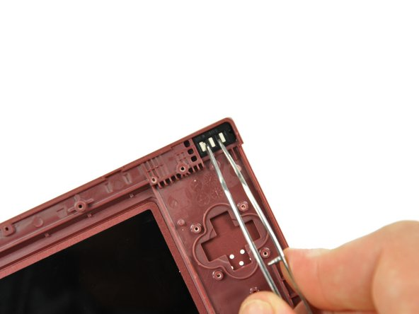 Using a pair of tweezers, remove the LED diffuser bracket and the LED diffuser from the upper case of the DSi XL.