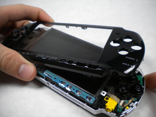 Insert a spudger between the front case and PSP, and slide the spudger along the perimeter of the front case to remove it.