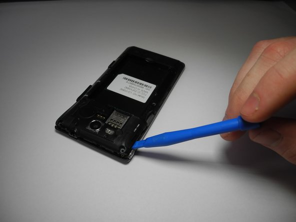 Once all the screws are removed, use a plastic opening tool to lift off the plastic cover. There are notches on the left side by the micro SD port.