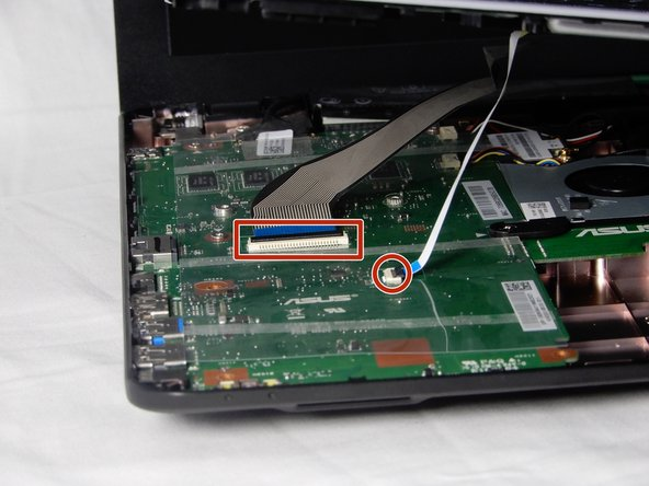 Disconnect the two keyboard ribbon bands from the motherboard before completing the disassembly. Flip both black hinges open to remove the ribbons. Lightly tug the bands out to complete the process.