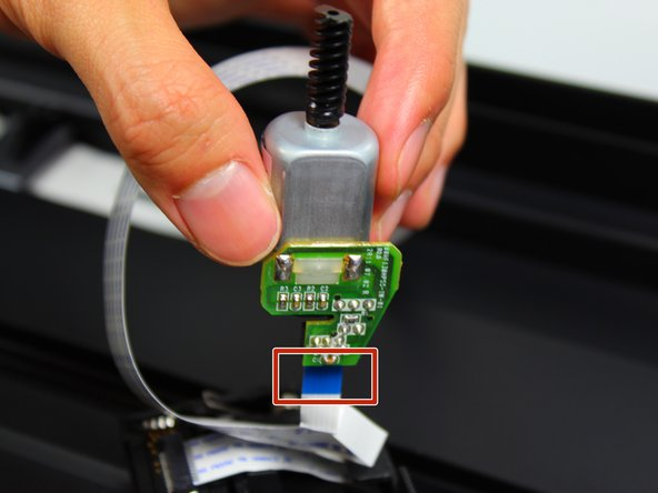 Remove the connector that is attached to the motor by pinching the blue part of the connector with two fingers and pulling it away from the circuit board.