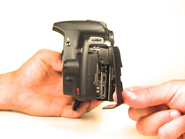 Use your fingers to gently detach the plastic component from the camera