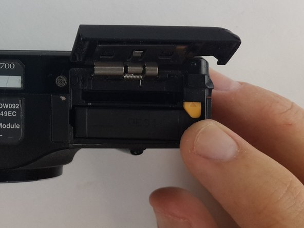 Push the yellow tab inside the battery compartment in the direction of the arrow. This will allow the battery to spring up.