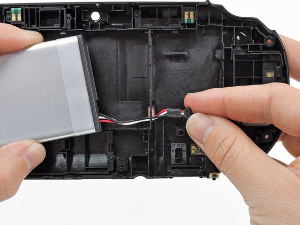 Image 3/3: Guide the battery wires through the hole in the back casing as you remove the battery.