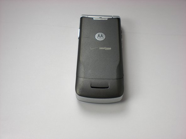 Push down on the silver tab located at the top center of the back of the Motorola K1m cellphone.