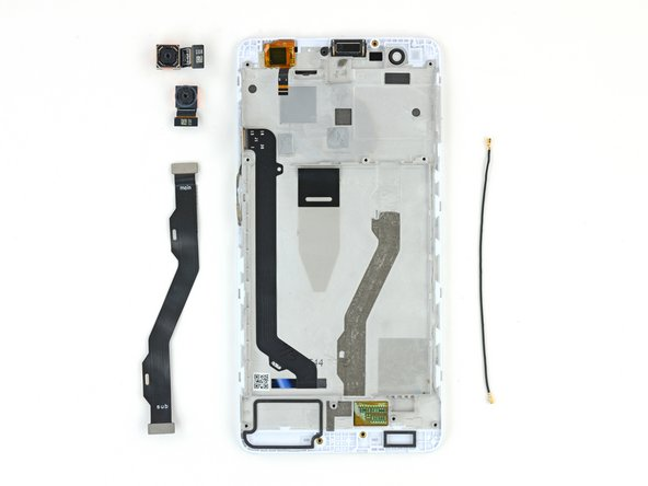 The primary camera is firmly glued to the midframe. It might be possible to extract it without first removing the motherboard, but only with some risk of pry damage to the motherboard.