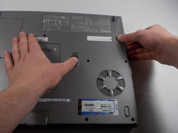 While holding the switch down, pull the battery out of the laptop, located in the upper right-hand corner.