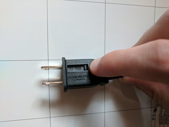 Slide open the fuse access cover on the top of the plug by moving it towards the end of the plug.