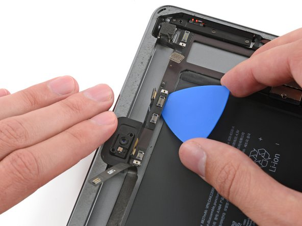 Slide the pick toward the front-facing camera connector, and stop at the bend in the logic board.