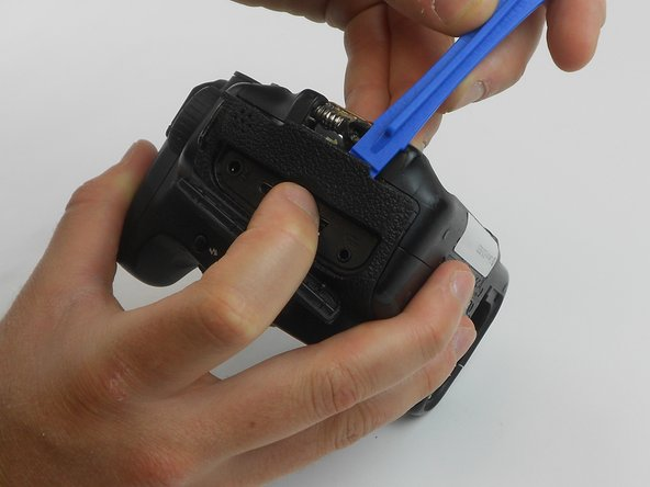 Using the plastic opening tool, carefully pull up the rubber grip around the port side of the camera.