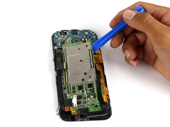 Use a plastic opening tool to gently pry the motherboard free of the display assembly.