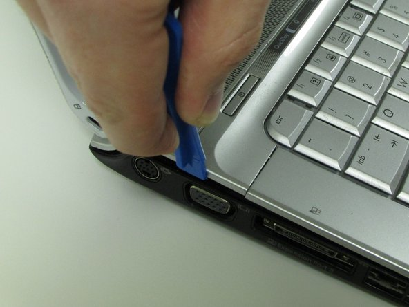Use plastic opening tool to pry open the plastic bar above the keyboard.