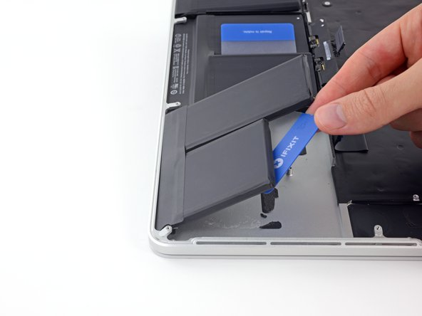 Flip the two de-adhered right-hand battery cells over the front edge of the MacBook Pro, if you haven't already.  This will allow access to the outside edge of the center cell.