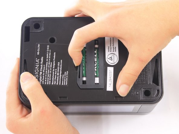 On the bottom of the clock, use your fingernail to push the battery cover to the right.