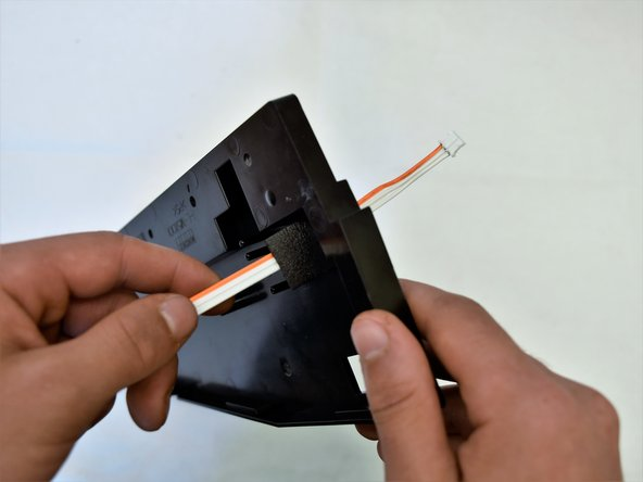 Run the white and orange cable through the innermost side panel and pull out