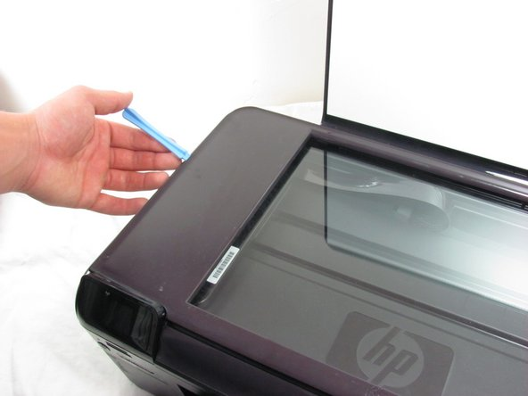 Using a small plastic prying tool, carefully pry the plastic frame surrounding the glass from the printer hood.