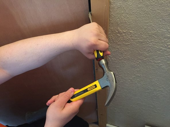Take the hammer and hit the handle end of the screwdriver until the pin can be pulled out. This may take a while depending on the door.