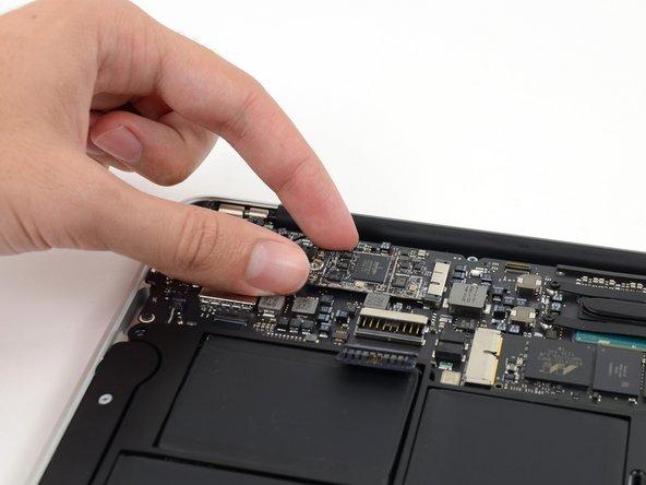 Hebe das freie Ende der AirPort/Bluetooth Karte etwas hoch und ziehe sie aus ihrem Anschluss auf dem Logic Board.