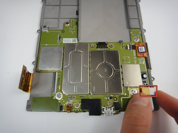 Image 1/2: Remove the white flex cable by gently lifting the yellow plastic connector.